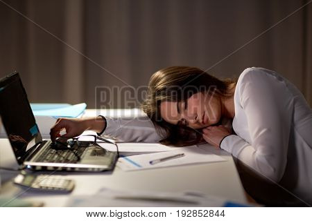 business, overwork, deadline and people concept - tired woman with laptop and papers sleeping on table at night office