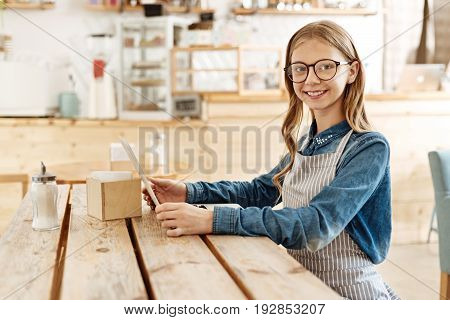 Interesting novelties. Gorgeous fair-haired girl in a striped apron sitting at the wooden table in a cafe and looking through a menu while looking at the camera with a cute smile