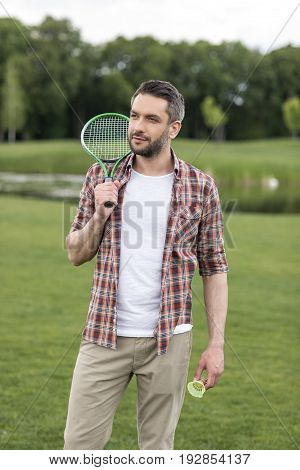 Handsome Bearded Man Holding Badminton Racquet On Shoulder And Looking Away