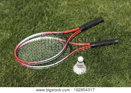 Close Up Of Badminton Rackets With Shuttlecock On Grass