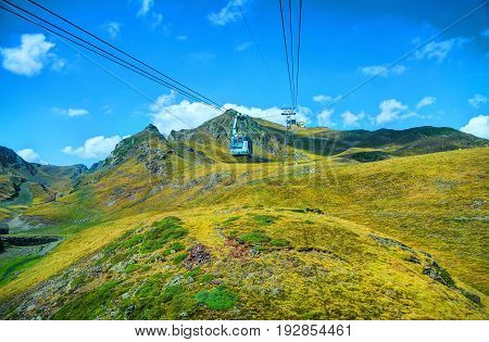 FRANCE SEP 29 2011: View on cable-way funicular cabin to Pyrennes mountains ski station observatoire Pic du Midi peak. Green yellow mountains hills. France holidays vacations tours car travel
