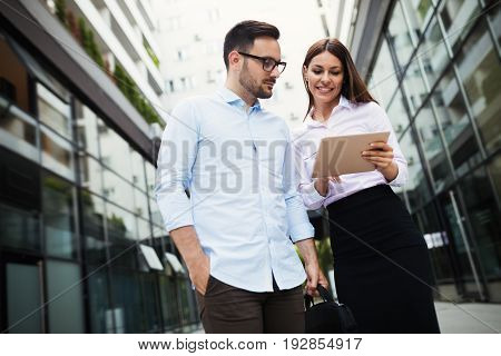 Picture of handsome man and beautiful woman as business partners standing outside