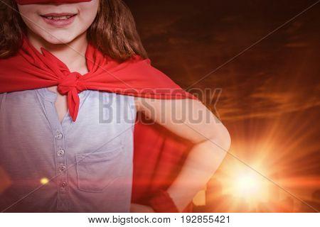Little girl pretending to be a superhero against buildings against sky during sunset