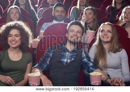 Young people smiling enjoying movie premiere at the local cinema entertainment emotions activity youth weekend happiness viewers friends lifestyle concept.