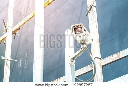 Surveillance cctv camera and security concept - Surveillance cctv camera on pole in building construction site with flare light effect and copyspace