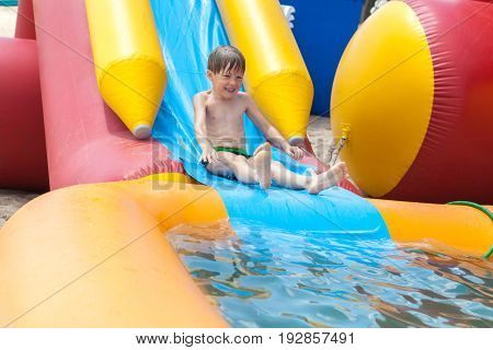 The boy is entertained outdoors bathed in an inflatable pool. Slides down from the slide into the water.