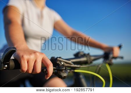 Close-up of a young slender woman sitting on bicycle, holding handlebars with hands against blue sky. Woman rides bicycle trip. Active life and recreation concept