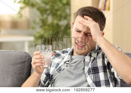 Man suffering head ache with a hand on forehead and holding a glass with a painkiller sitting on a couch at home