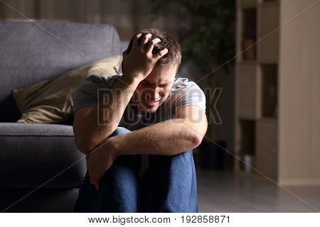 Sad man lamenting sitting on the floor in the living room in a house indoor with a dark background