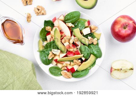 Healthy breakfast with fruit salad from apples avocado spinach and nuts on light background top view