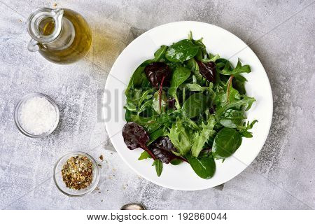 Healthy green salad with leaves of spinach arugul on light background. Top view