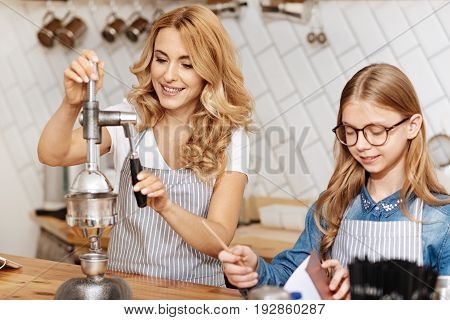 Best coffee. Beautiful young woman using a coffee-making device while her adorable daughter standing next to her behind the coffee bar counter and putting down the algorithm
