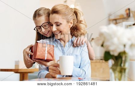 Love you mum. Winsome teenage girl hugging her dear mother from behind and giving her a beautifully wrapped gift for Mothers Day while the mother looking at it with affection