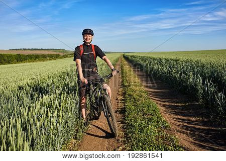 Young cyclist standing with mountain bike on background of beautiful landscape. Sportsman dressed in the black sportwear, with helmet and backpack. Blue sky with clouds like a background. Concept of the healthy lifestyle.