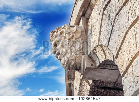 Historic building detail man head with blue cloudy sky