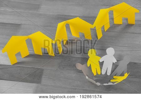 Paper cutout figures standing in circle by paper houses on table