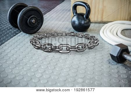 3d image of round shiny silver chain against excercise equipment on the floor