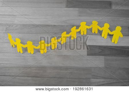 High angle view of yellow paper cutout human chain on wooden table