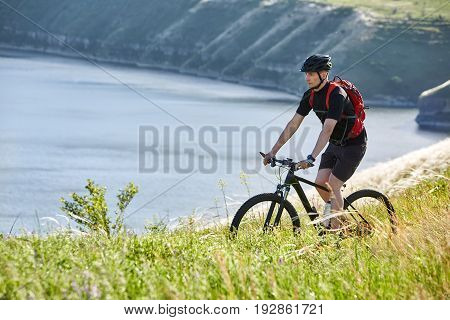 Attractive cyclist riding the mountain bike on the summer trail above the river. Sportsman in the black sportwear, with helmet and backpack. Beautiful landscape like a background. Concept of the healthy and active lifestyle.