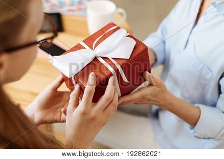 Token of appreciation. The close up of two pairs of dainty female hands holding an intricately wrapped gift box tied up with a white bow