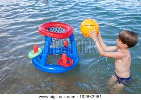 A boy on the beach playing in the water with an inflatable ball. Little boy playing basketball in the water. Boy beach water game ball.