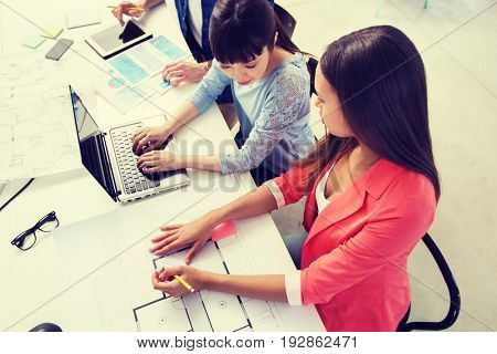 business, startup and people concept - creative team with laptop and blueprint at office