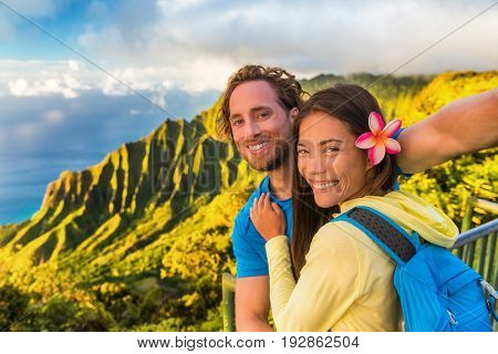 Na pali hikers couple tourists taking selfie at Napali lookout in Kauai Hawaii. Travel friends taking smartphone picture at famous destination Kalalau hawaiian attraction.