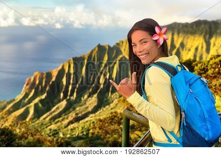 Hawaii travel tourist. Na pali hiker girl tourist doing shaka hawaiian hand sign at Napali lookout in Kauai. Asian woman backpacker hiking with bag at famous destination Kalalau hawaiian attraction.