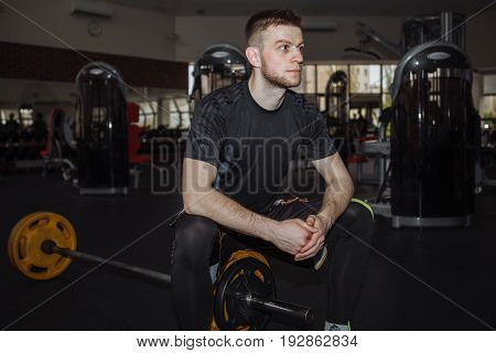 Portrait of a man in the gym. The guy sat down to rest before performing strength exercises.