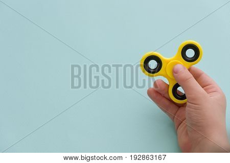 Child's hand spinning a fidget spinner device on light blue background. Top view. Playing with a yellow hand spinner fidget toy