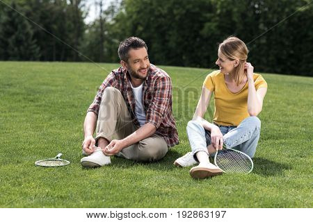 Happy Caucasian Couple With Badminton Racquets Resting Together In Park