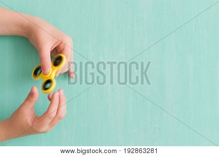 Child's hand spinning a fidget spinner device on turquoise background. Top view. Playing with a yellow hand spinner fidget toy