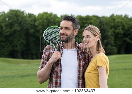 Happy Young Couple With Badminton Racquet Standing Together In Park