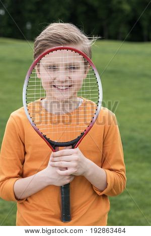 Adorable Smiling Boy Looking Through Badminton Racquet