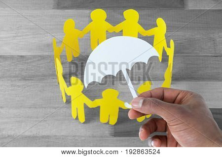hand holding an umbrella in paper against yellow paper cut out figures formimg circle on wooden table