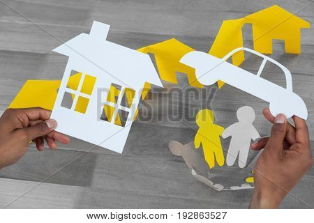 man holding a car and a house in paper against paper cutout figures standing in circle by paper houses