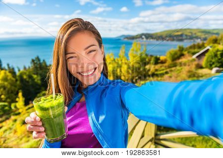 Healthy green smoothie juice drinking selfie girl taking picture clean food diet healthy nutrition. Asian woman eating fresh spinach vegetable juicing in beautiful outdoors autumn nature.