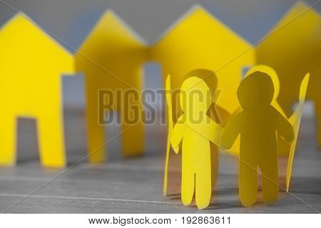 Group of paper figures and houses on wooden table