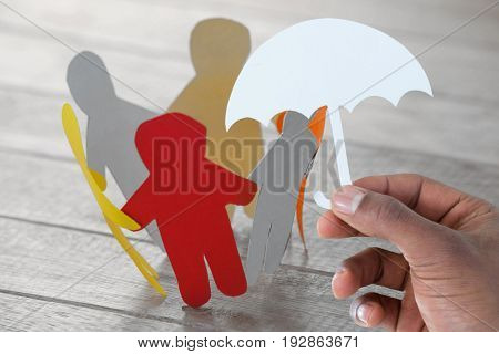 hand holding an umbrella in paper against multi colored paper cut out figures forming circle on wooden table