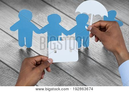 hands holding a schoolbag and an umbrella in paper against white paper cut out figures on wooden table