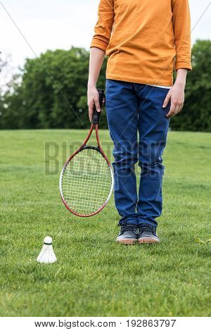 Cropped Shot Of Little Boy Holding Badminton Racquet And Standing On Green Grass With Shuttlecock Ne