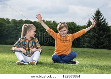 Adorable Little Children With Badminton Racquets Having Fun While Sitting On Grass
