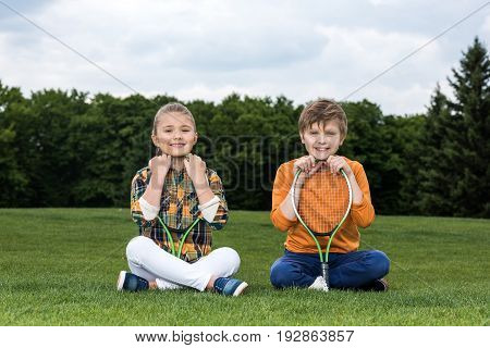 Adorable Little Children With Badminton Racquets Sitting On Grass And Smiling At Camera