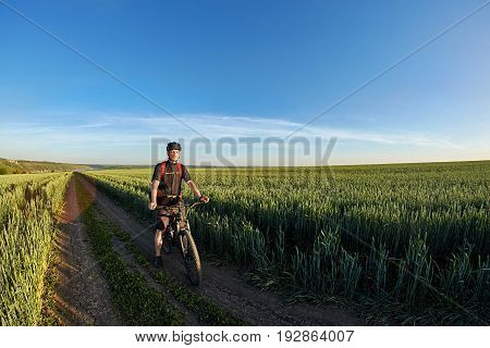 Attractive cyclist standing with bike and observing the view against blue sky. Young sportsman dressed in the black sportwear and sporty shoes, with helmet and backpack. Travel in the countryside in summer season. Concept of the health lifestyle.