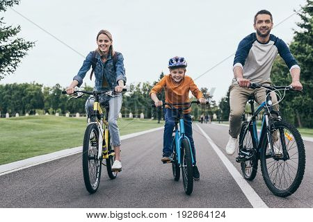 Smiling Parents And Little Son Riding Bicycles Together In Park
