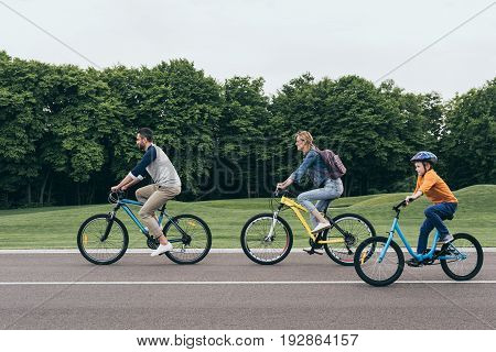 Side View Of Smiling Parents And Little Son Riding Bicycles Together In Park