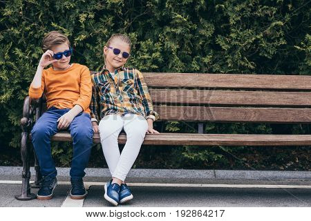 Adorable Kids In Sunglasses Sitting Together On Bench At Park