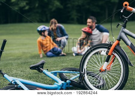 Happy Family Spending Time At Park, Selective Focus On Bicycles At Foreground