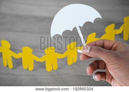 hand holding an umbrella in paper against paper cut out figures forming chain on wooden table