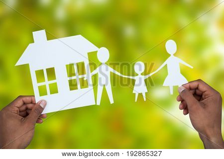 hands holding a family with her house in paper against detail shot of bright green leaves